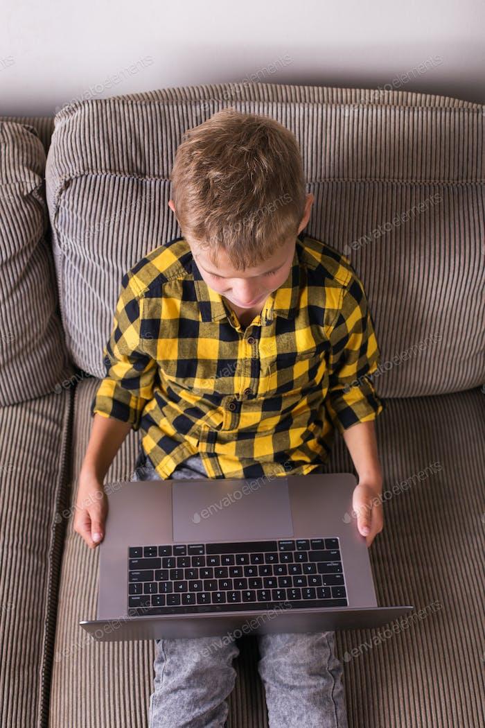 Junge sitzt auf einer Couch und schreibt in einem Notizbuch