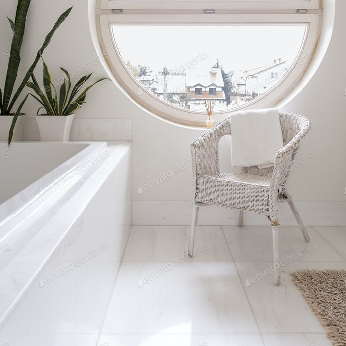 Spacious white bathroom with round window