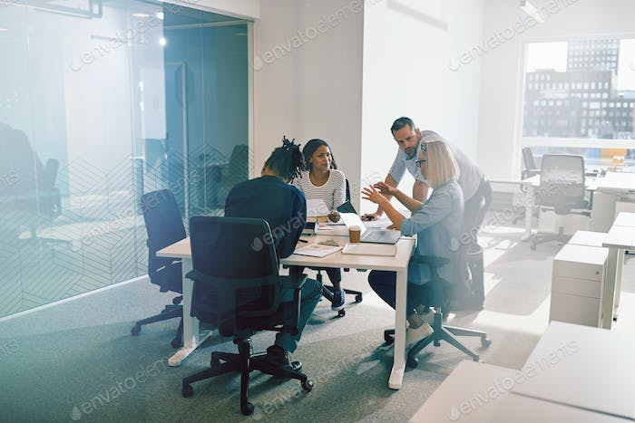 Work colleagues discussing business together during an office meeting