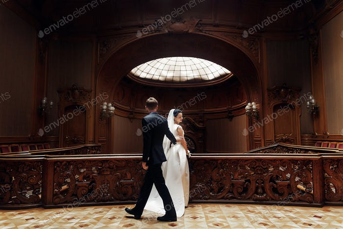 Bride and stylish groom posing in amazing rich room