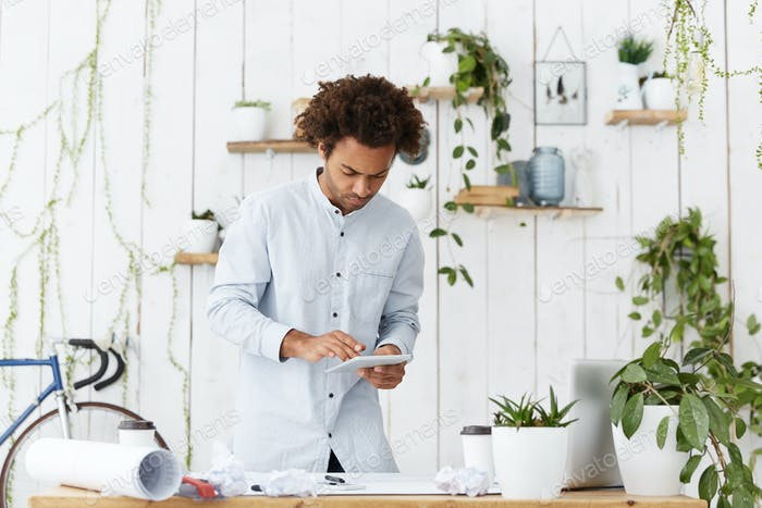 Serious Afro American engineer, designer or architect with funky hairstyle standing against office i