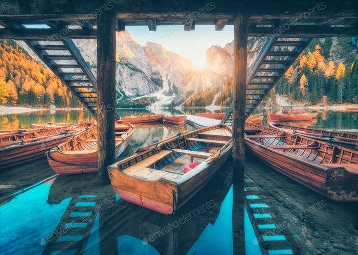 Wooden boats near the house in Braies lake at sunrise