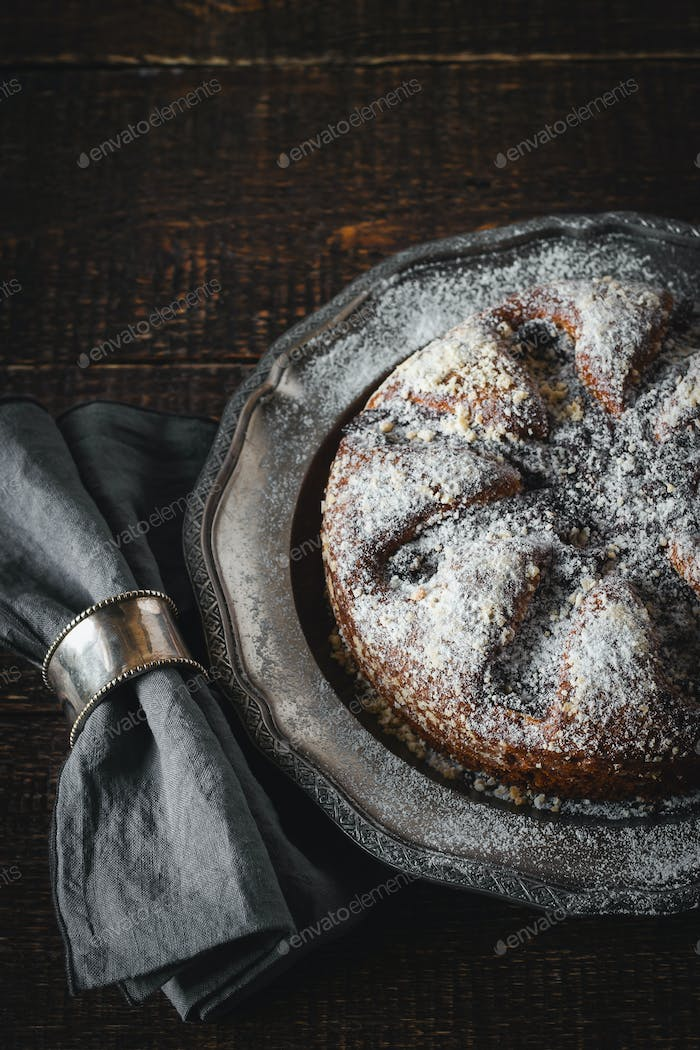 Cake with icing sugar with napkin in the vintage metal ring vertical