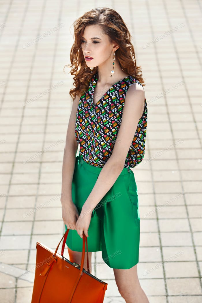 Beautiful women dressed in stylish green shorts and a bright top holding orange bag is walking in