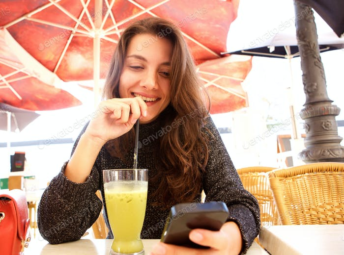 Close up happy woman looking at cellphone with cold drink at cafe