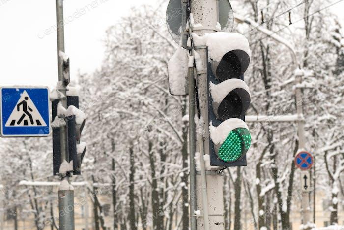 Eine funktionierende Ampel an einer Stadtstraße im Winter. Die Ampel ist grün