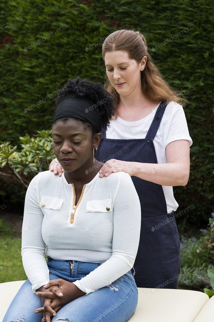 Therapeut berührt die Schultern eines Klienten in einer Outdoor-Therapiesitzung