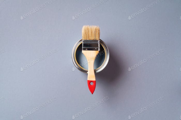 Brush and open paint can with on pastel background. Top view, copy space. Appartment renovation