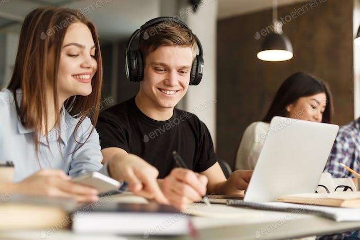 fröhliche Schüler machen Hausaufgaben in der Bibliothek