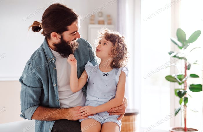 A small girl with young father at home, talking. Copy space.