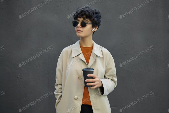 Lifestyle fashion portrait of young stylish hipster female with short dark curly hair