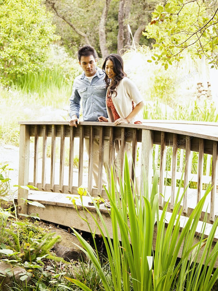 Chinese couple on bridge overlooking a stream in nature