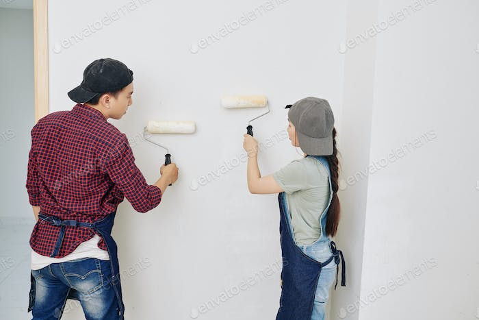 People applying matte white paint