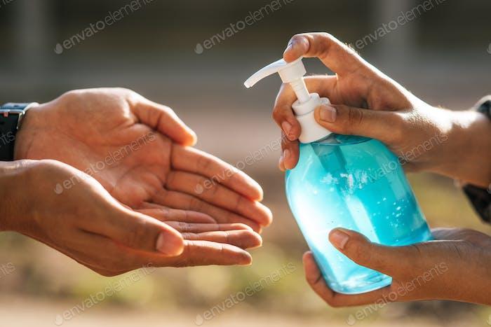 Manos en la botella de gel para lavarse las manos y apretar para que otros se laven las manos.