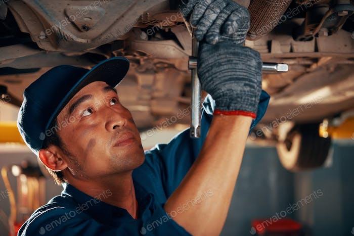 Mechanic reparing car in garage