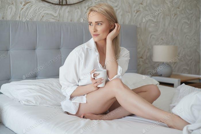 Schöne blonde Frau trinken einen Kaffee während sitzen auf ihrem Bett zu Hause