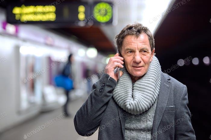 Senior man at the underground platform, talking on phone