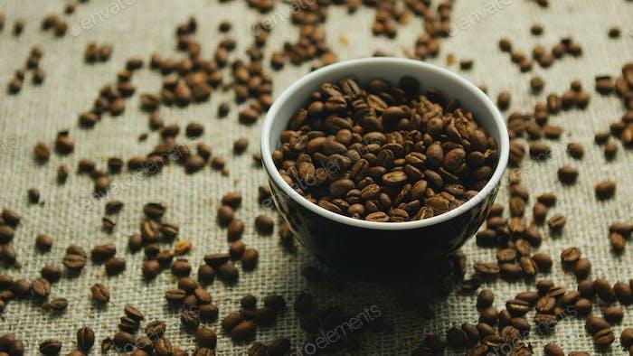 Taza de granos de café sobre lienzo