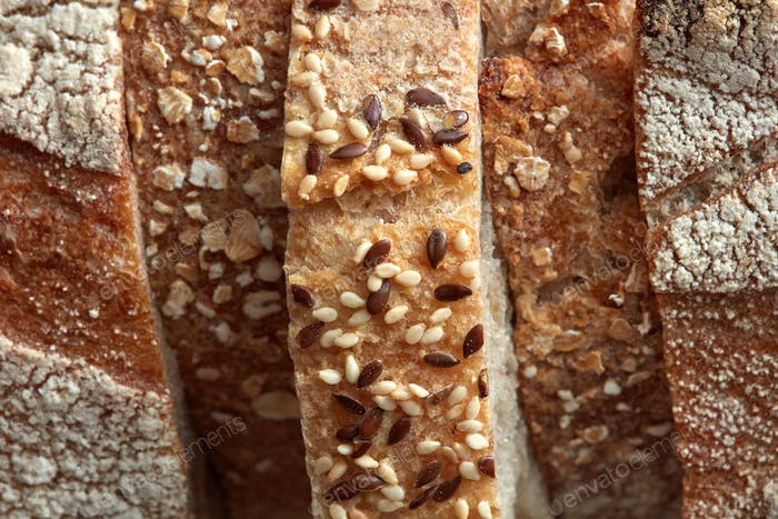 Crispy organic bread slices with flax seeds and sesame macro photo. Flat lay