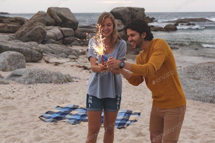 Paar spielen mit Feuer Cracker beim Stehen am Strand