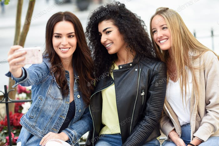 Multi-ethnic young women taking a selfie photograph together out