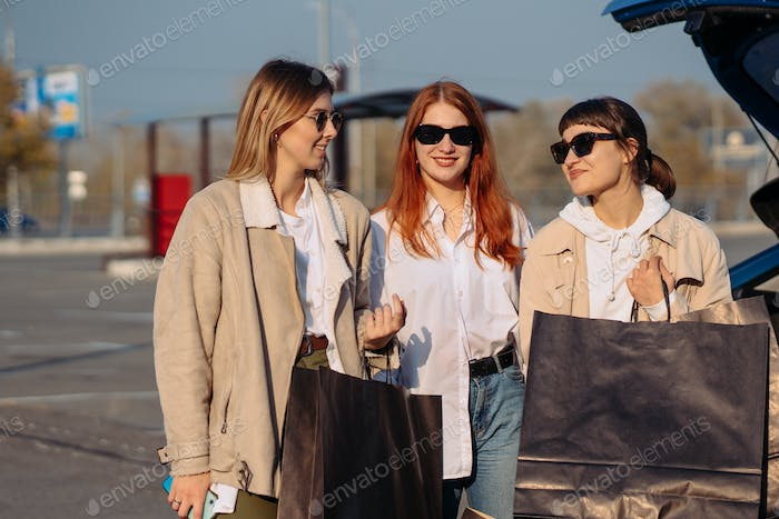 Young women at the car with shopping bags