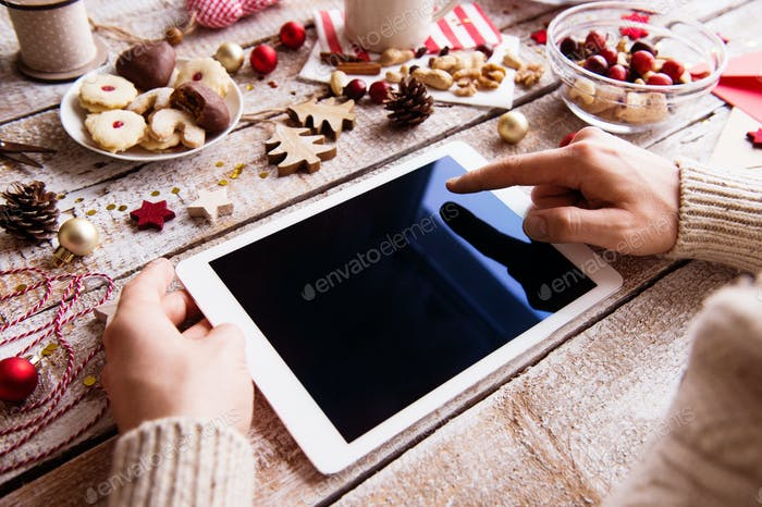 Christmas composition with tablet on a wooden background.