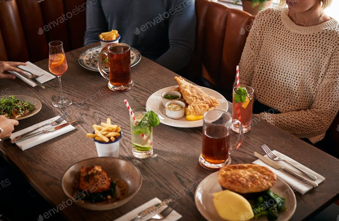 Близко вверх друзей встреча для еды в традиционном английском пабе