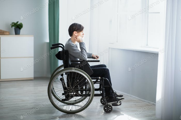 Side view of impaired teenage boy in wheelchair feeling desperate and lonely, looking out window at