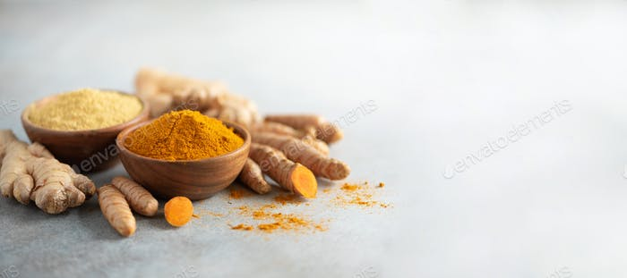 Turmeric and giger powder in wooden bowl and fresh turmeric root on grey concrete background. Banner