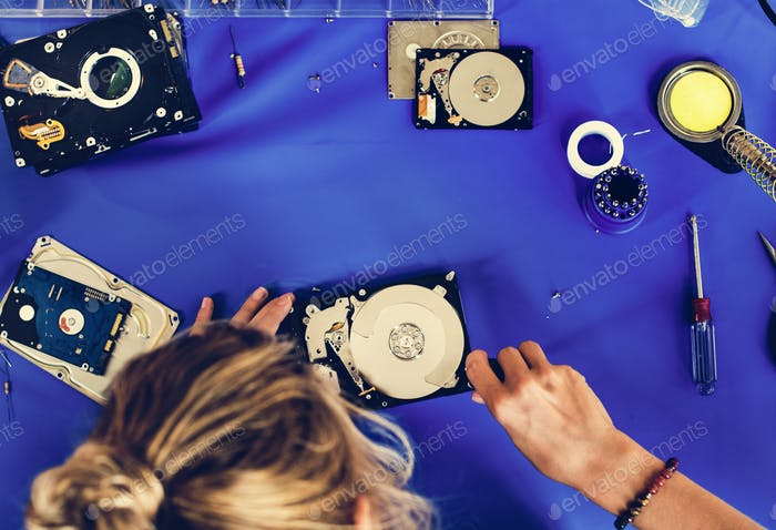 Caucasian technician fixing HDD at workstation