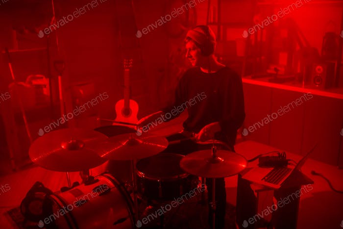 Young man in casualwear and headphones sitting by drumset in red lit garage