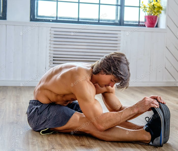 Shirtless athletic man warming up on a floor.
