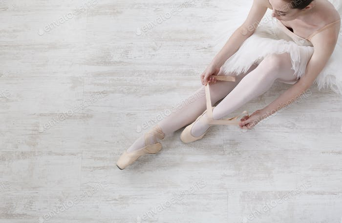 Ballerina puts on pointe ballet shoes, graceful legs