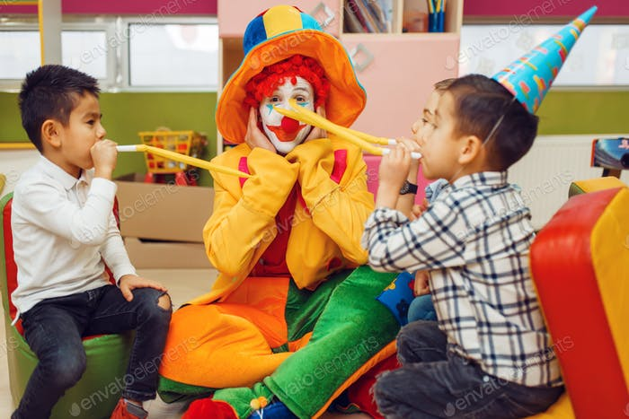 Lustiger Clown mit Kindern bläst in die Röhren