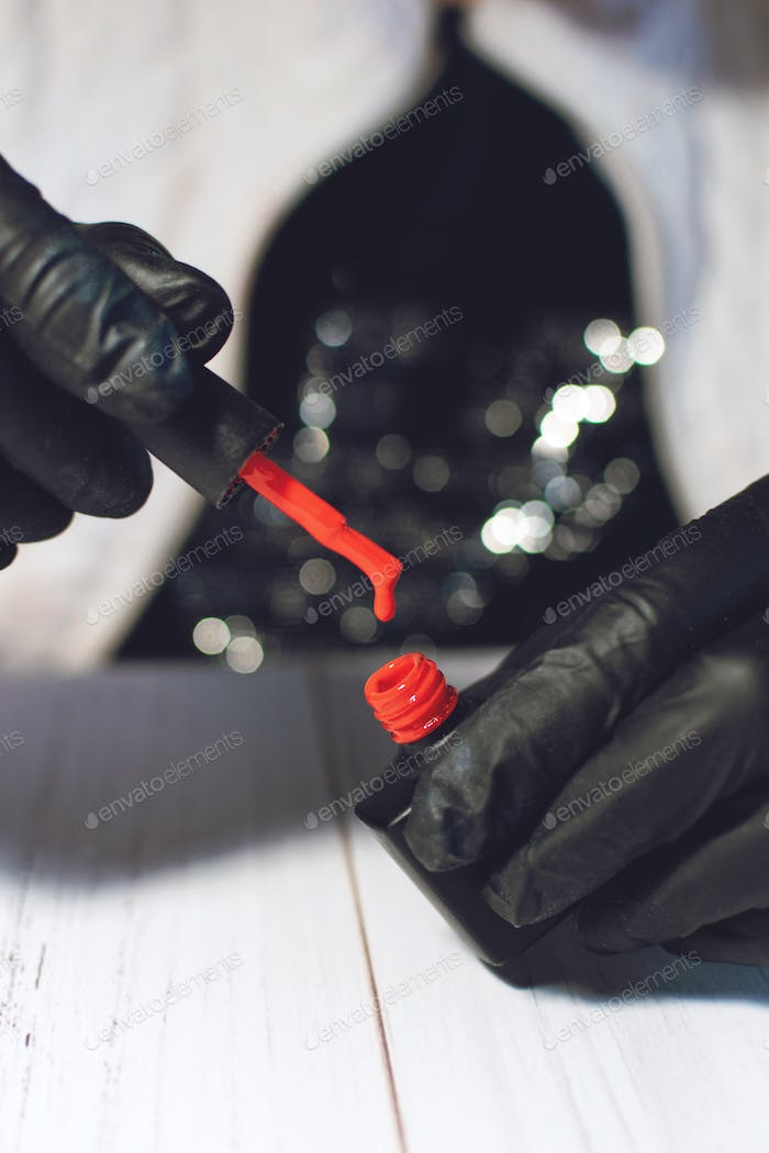 Manicure specialist in black gloves holding a bottle with red gel nail varnish. Close up of red gel