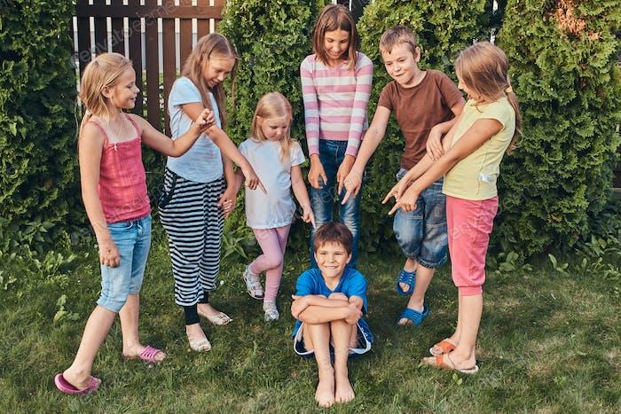 Gruppe von glücklichen kleinen Freunden, die Spaß auf dem Hof haben.