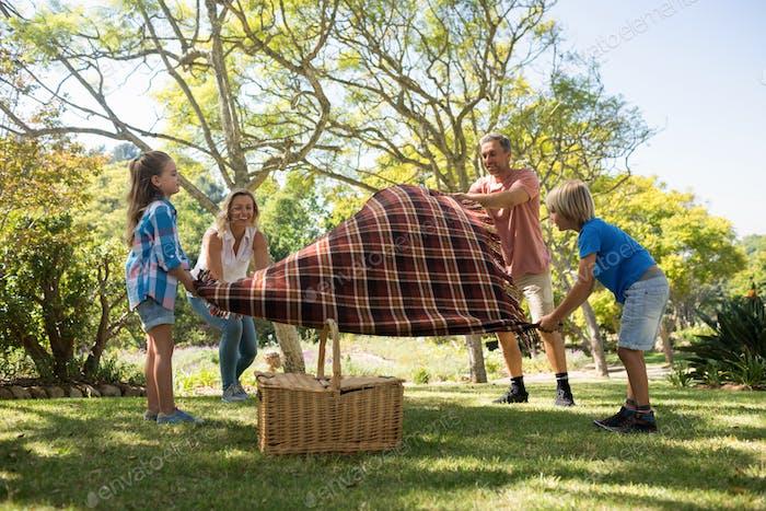 Familie verbreitet die Picknickdecke