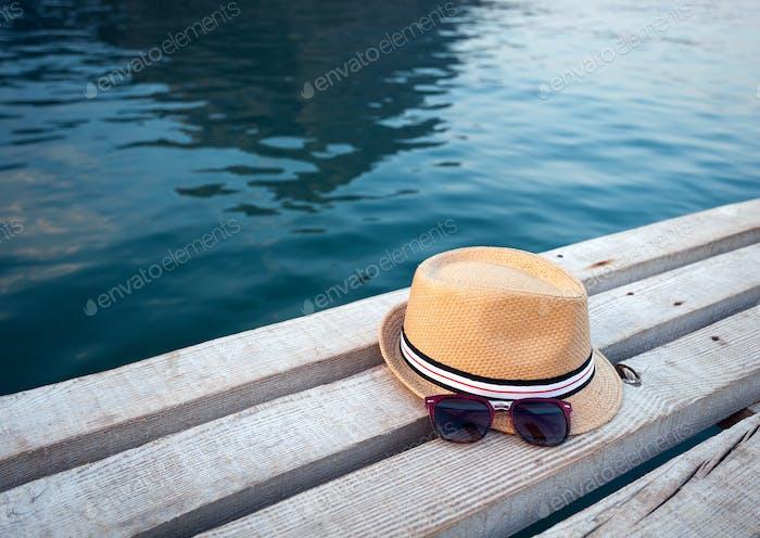 Sonnenbrille und Hut auf der Holzstruktur im Sommer