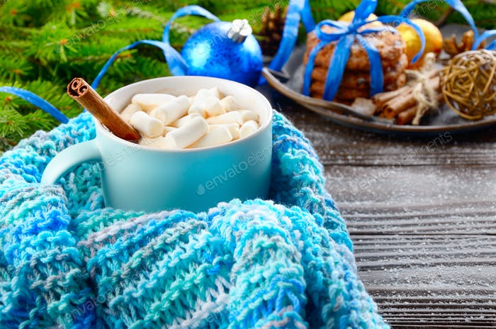 Christmas background of blue hot chocolate mug with marshmallows in knitted scarf