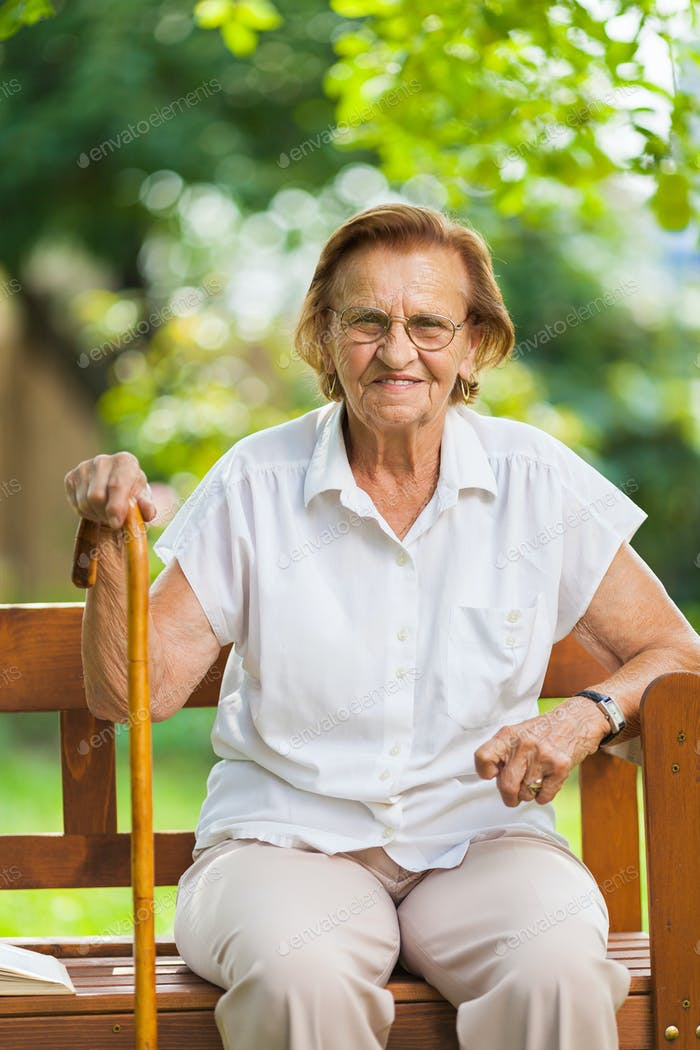 Elderly woman sitting and relaxing on a bench in park