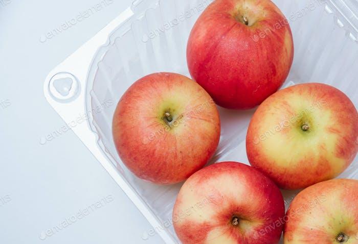 Red apple in plastic box