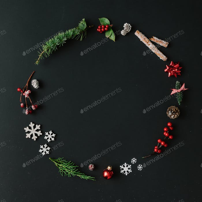 Christmas round frame made of natural winter things on dark blackboard. Flat lay. Christmas concept.