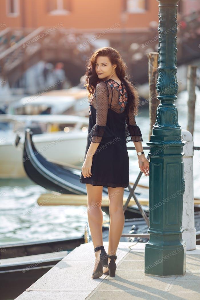 Reisetouristin auf Pier gegen schöne Aussicht auf venezianischen Chanal in Venedig, Italien
