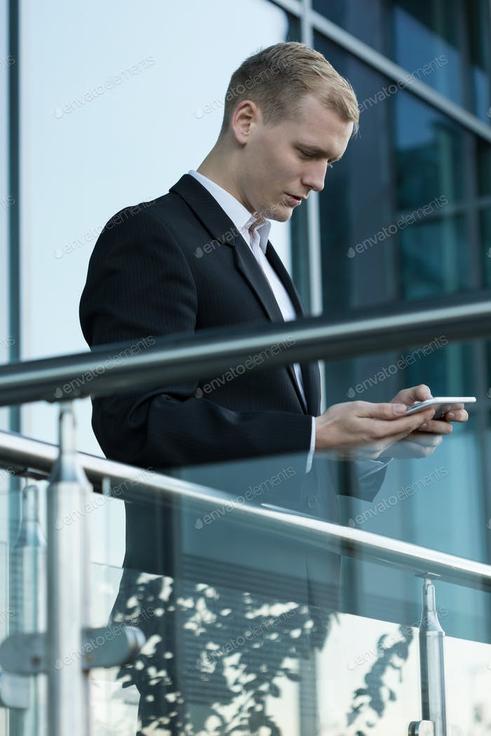 Businessman using phone outside the building