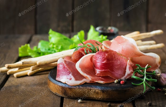 Slices of Prosciutto on old wooden background