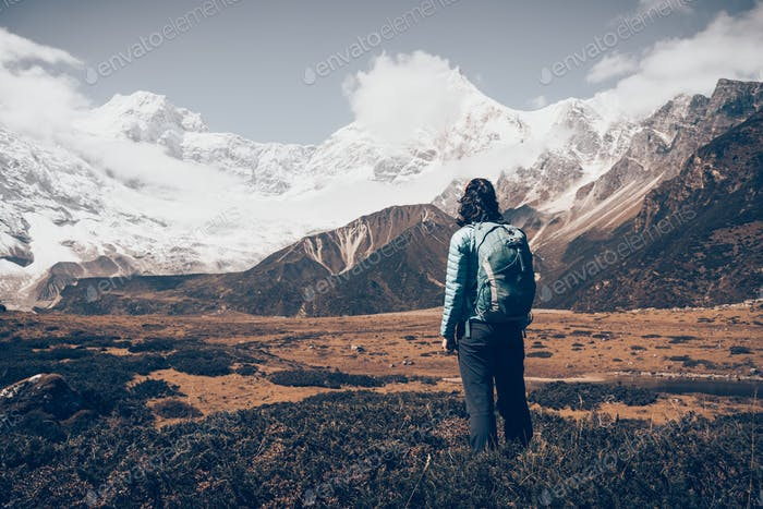 Standing young woman with backpack and mountains
