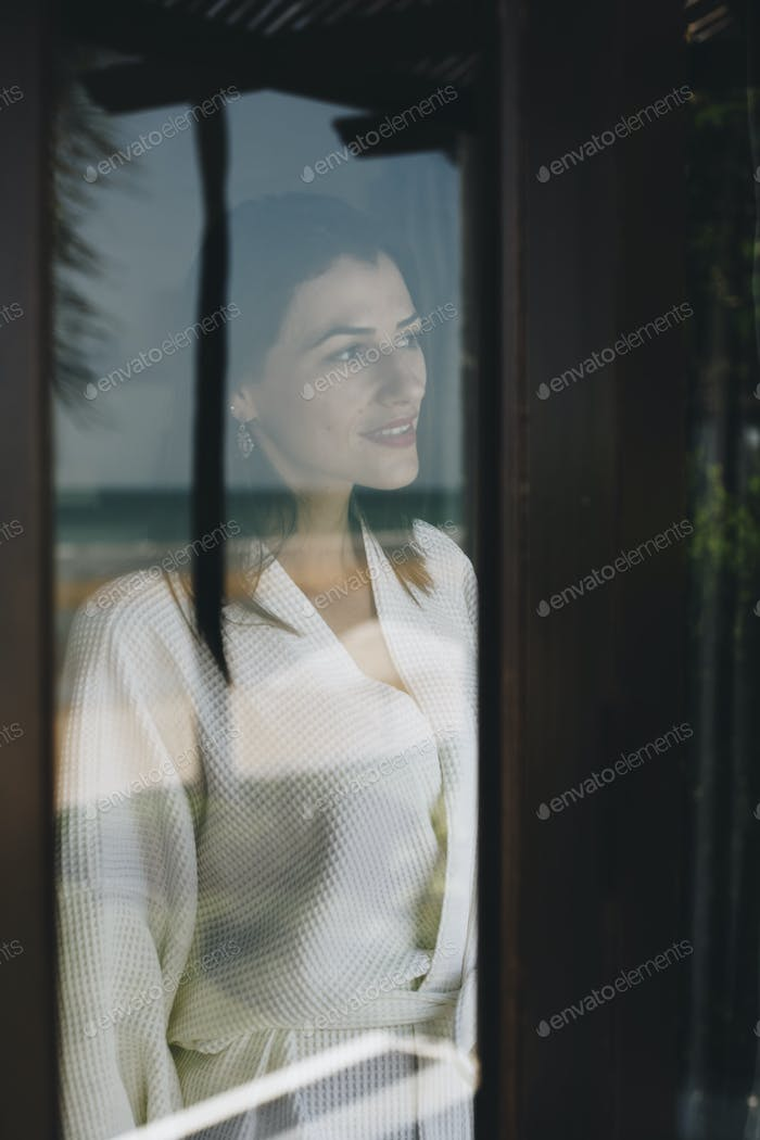 Woman looking out her hotel room window