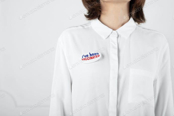 Middle age caucasian female in shirt with  button pin I've been vaccinated