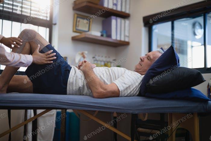 Hände von weiblichen Therapeuten messen Knie, während ältere männliche Patienten auf dem Bett liegend